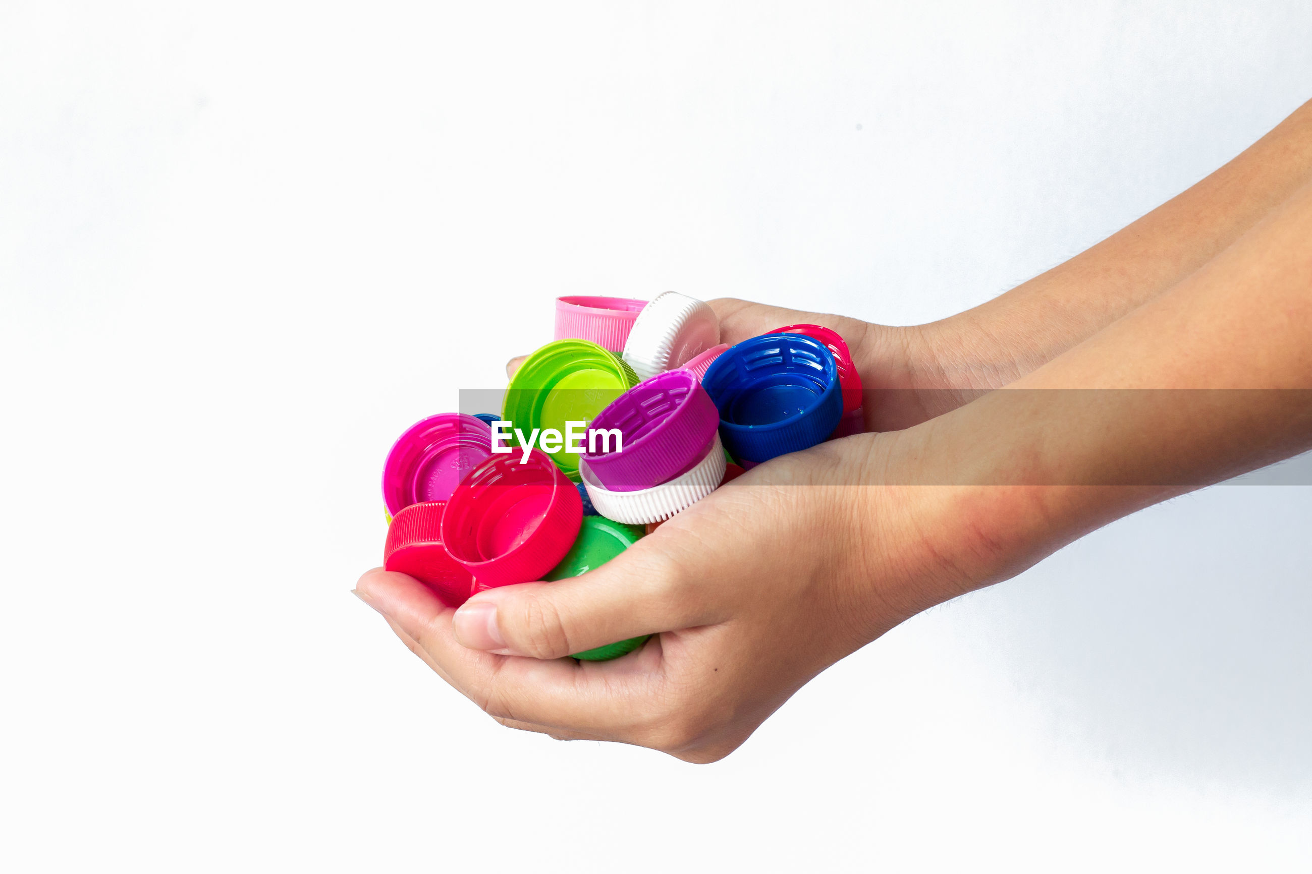 Cropped hands of person holding multi colored bottle caps against white background