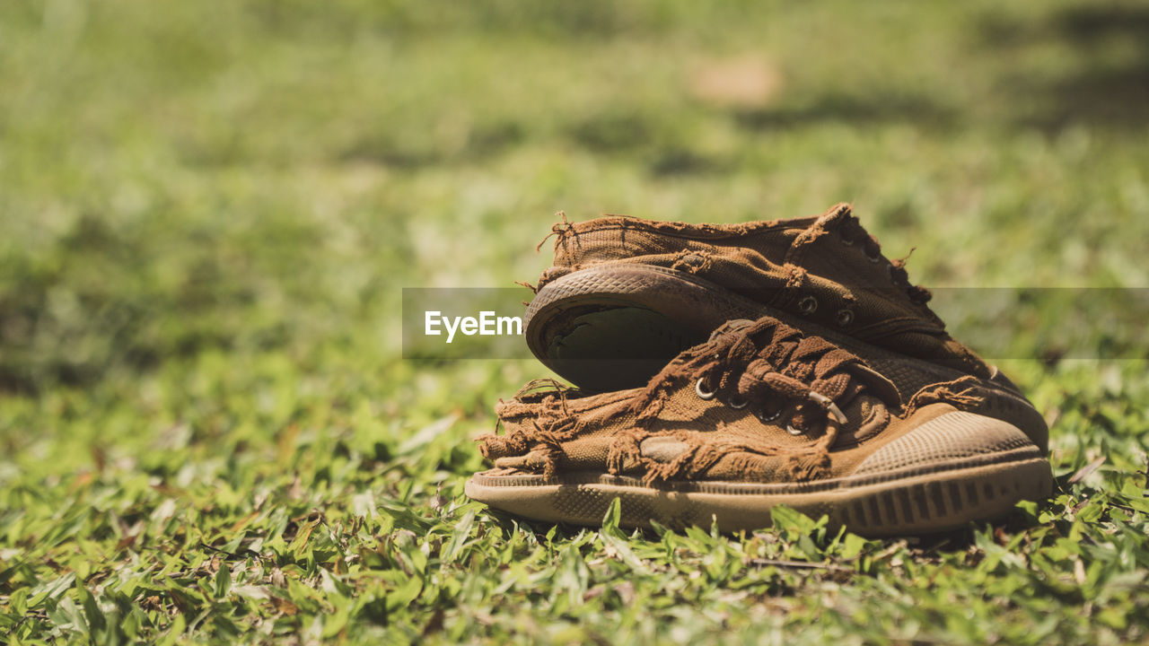 Close-up of torn shoes on field