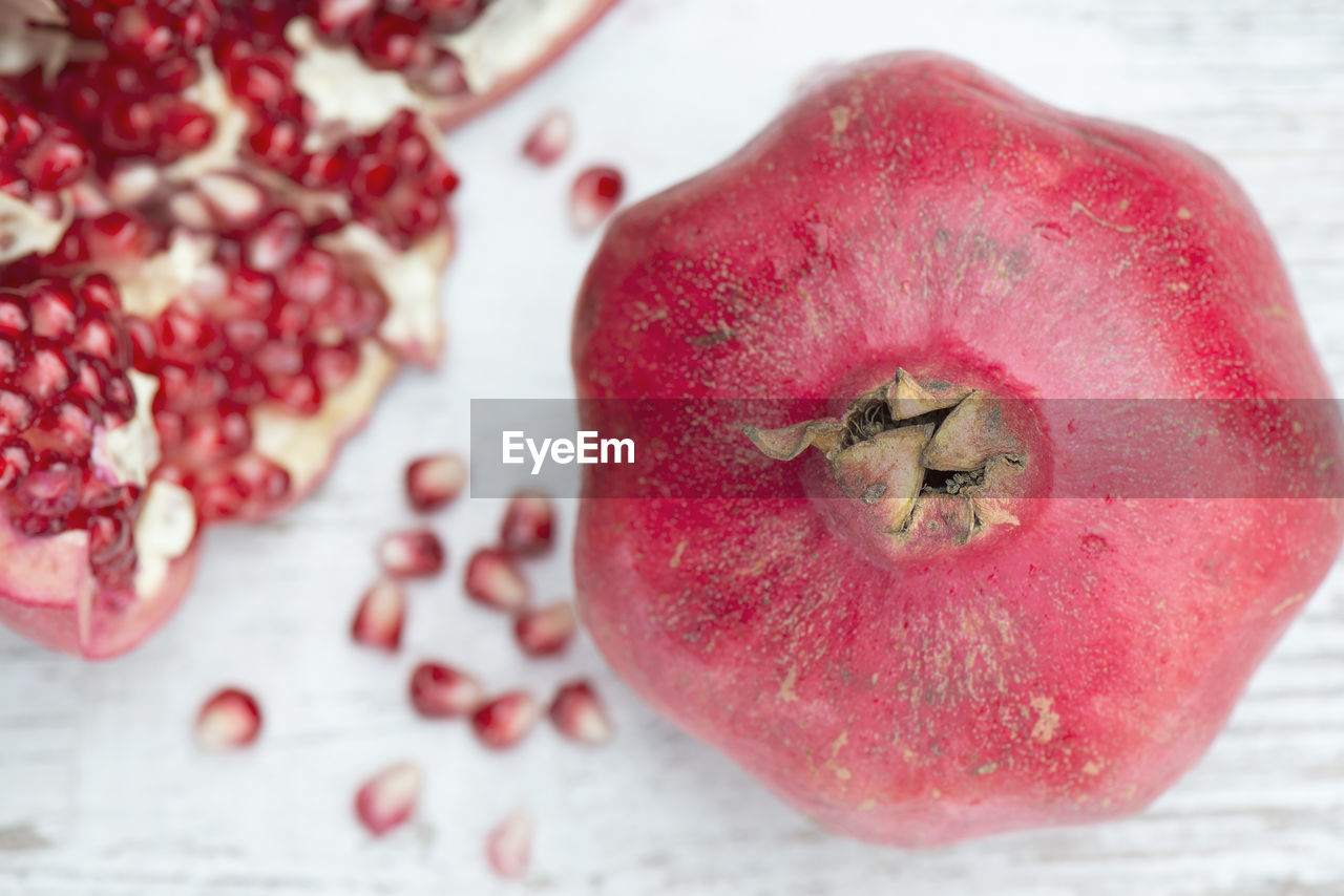 food and drink, food, healthy eating, fruit, freshness, wellbeing, close-up, red, still life, pomegranate, no people, seed, indoors, table, pomegranate seed, pink color, focus on foreground, apple - fruit, slice, cross section, ripe
