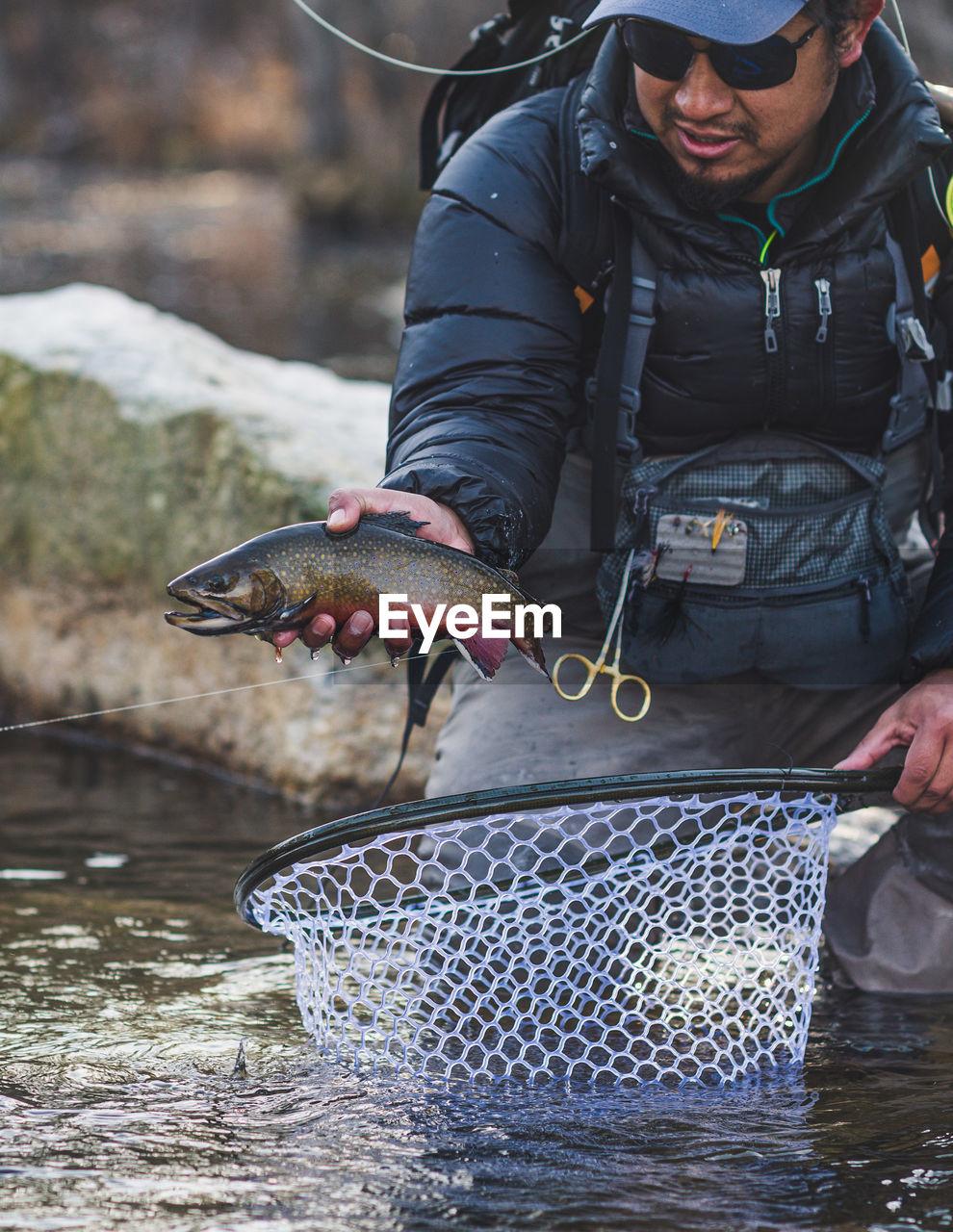 FULL LENGTH OF MAN HOLDING FISH AT WATER