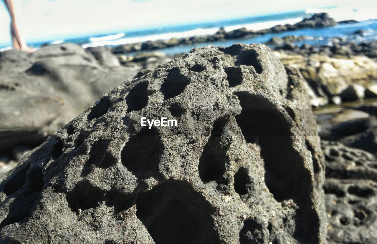 beach, shore, sand, nature, focus on foreground, sea, day, outdoors, no people, sunlight, rock - object, close-up, beauty in nature, tranquility, textured, sky, water, pebble beach