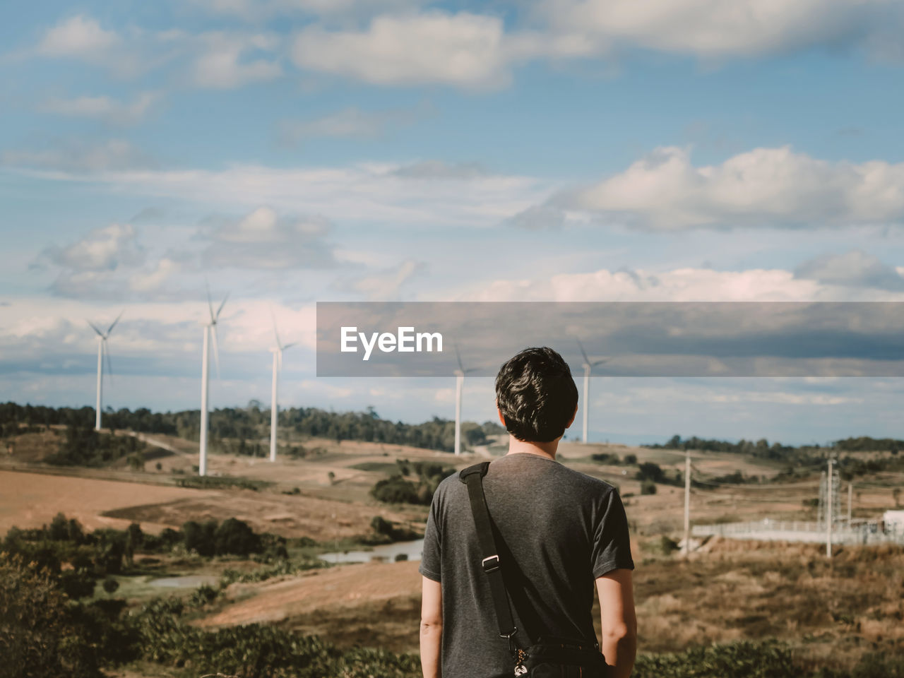 Asian man travel stand pose and see to sky for wait his girlfriend with wind turbine background