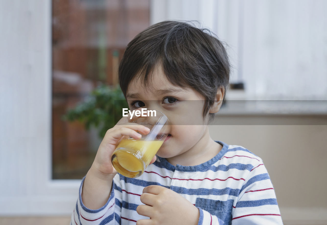 Portrait of boy drinking juice at home