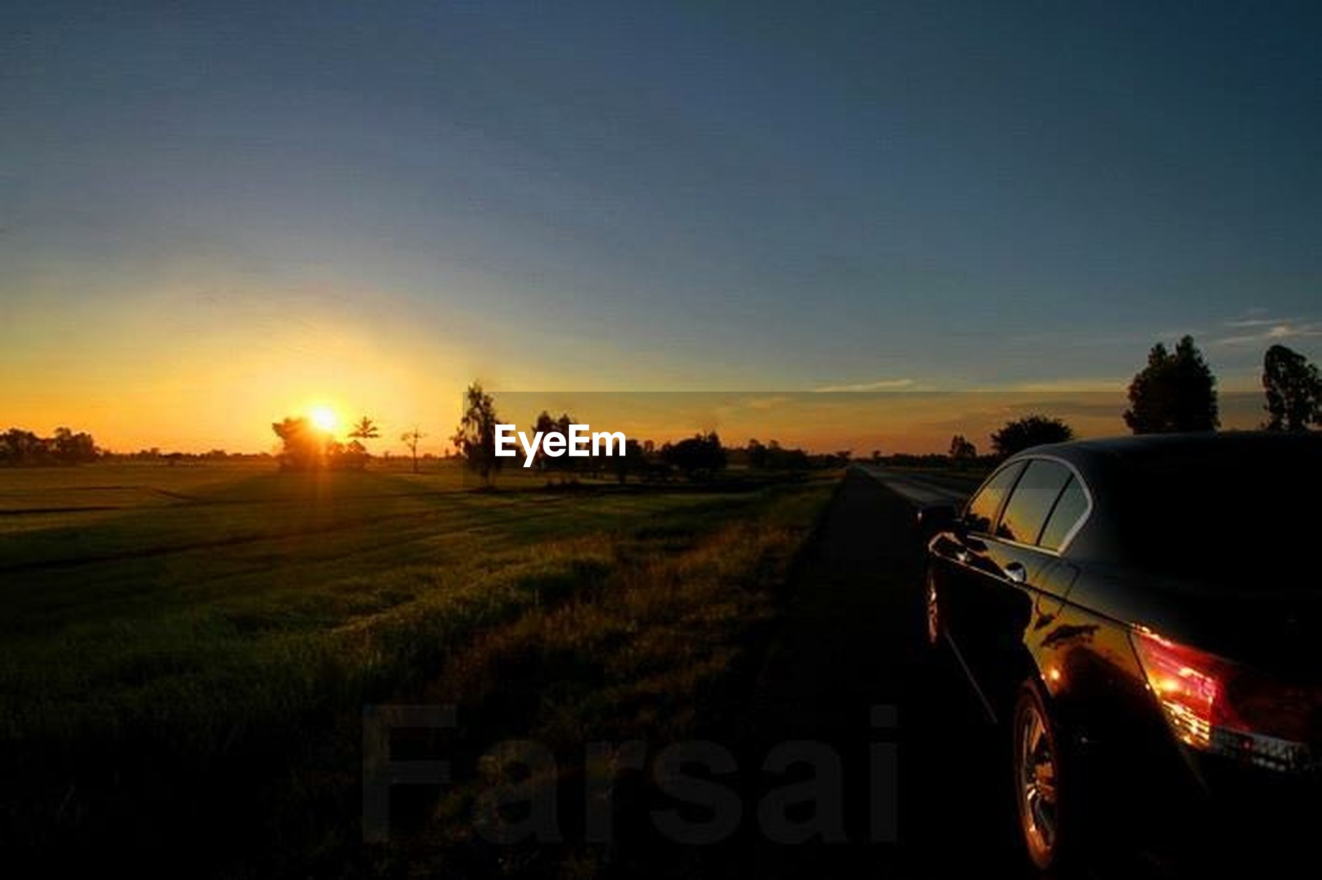 sunset, transportation, land vehicle, landscape, sky, car, mode of transport, silhouette, copy space, orange color, scenics, tree, sun, tranquil scene, field, road, beauty in nature, clear sky, tranquility, nature