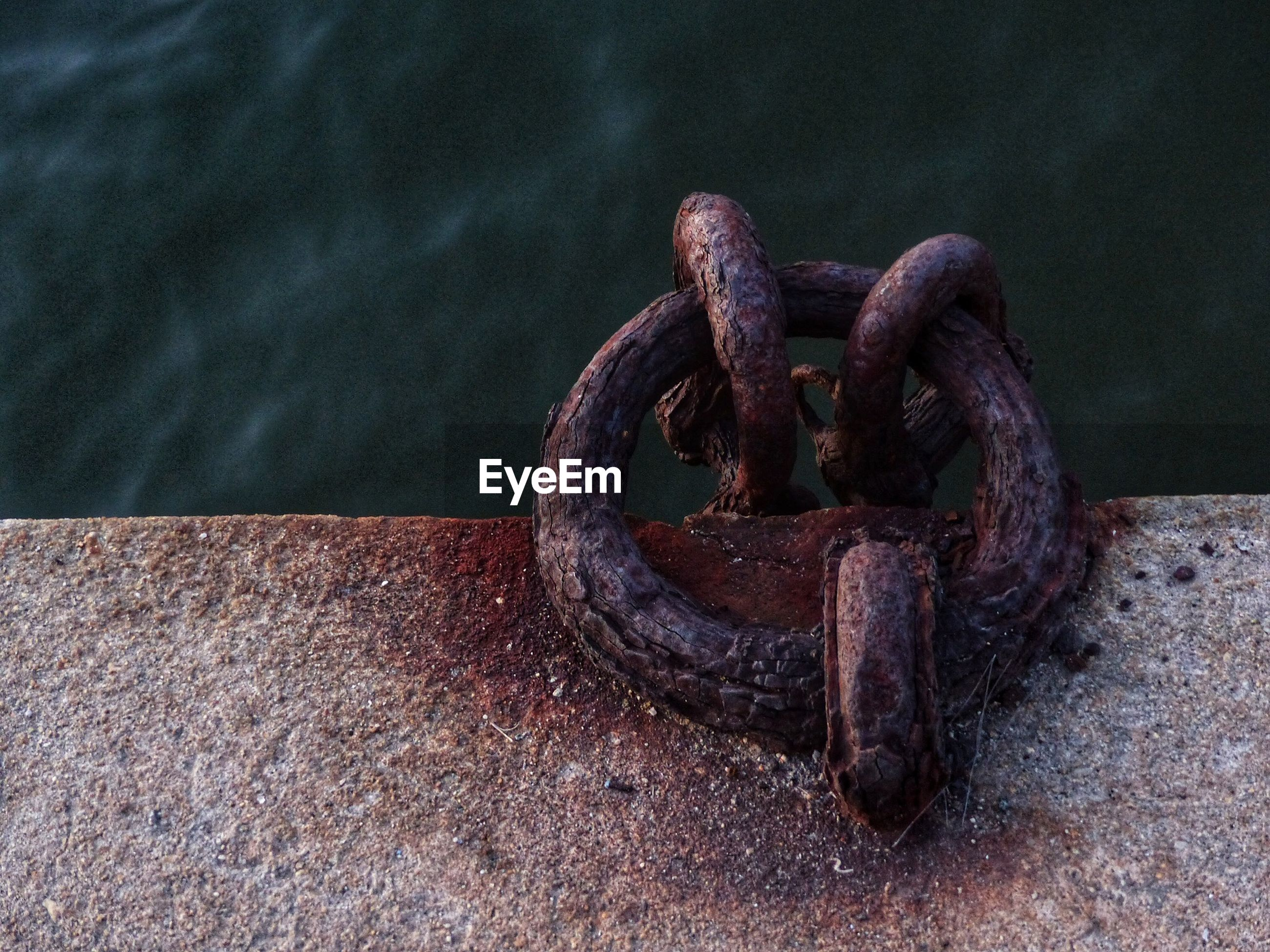Close-up of mooring ring mounted in retaining wall by river