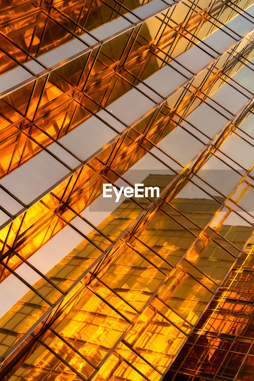 low angle view, no people, sky, full frame, yellow, architecture, orange color, built structure, sunset, pattern, backgrounds, cloud - sky, nature, building exterior, outdoors, building, sunlight, city, metal, modern