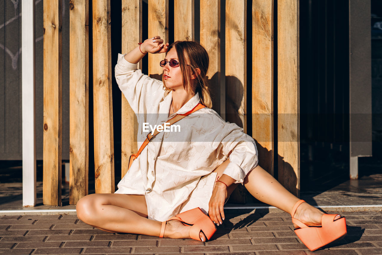 Young woman sitting against planks