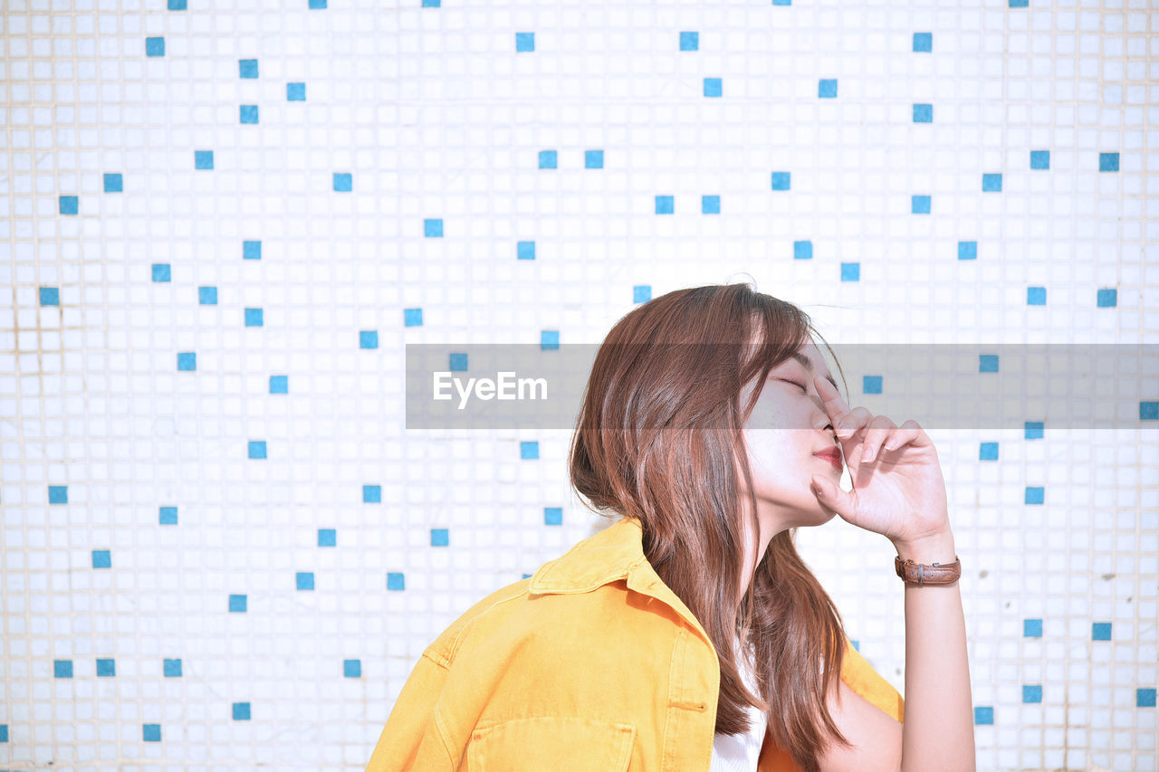 Woman by tiled wall