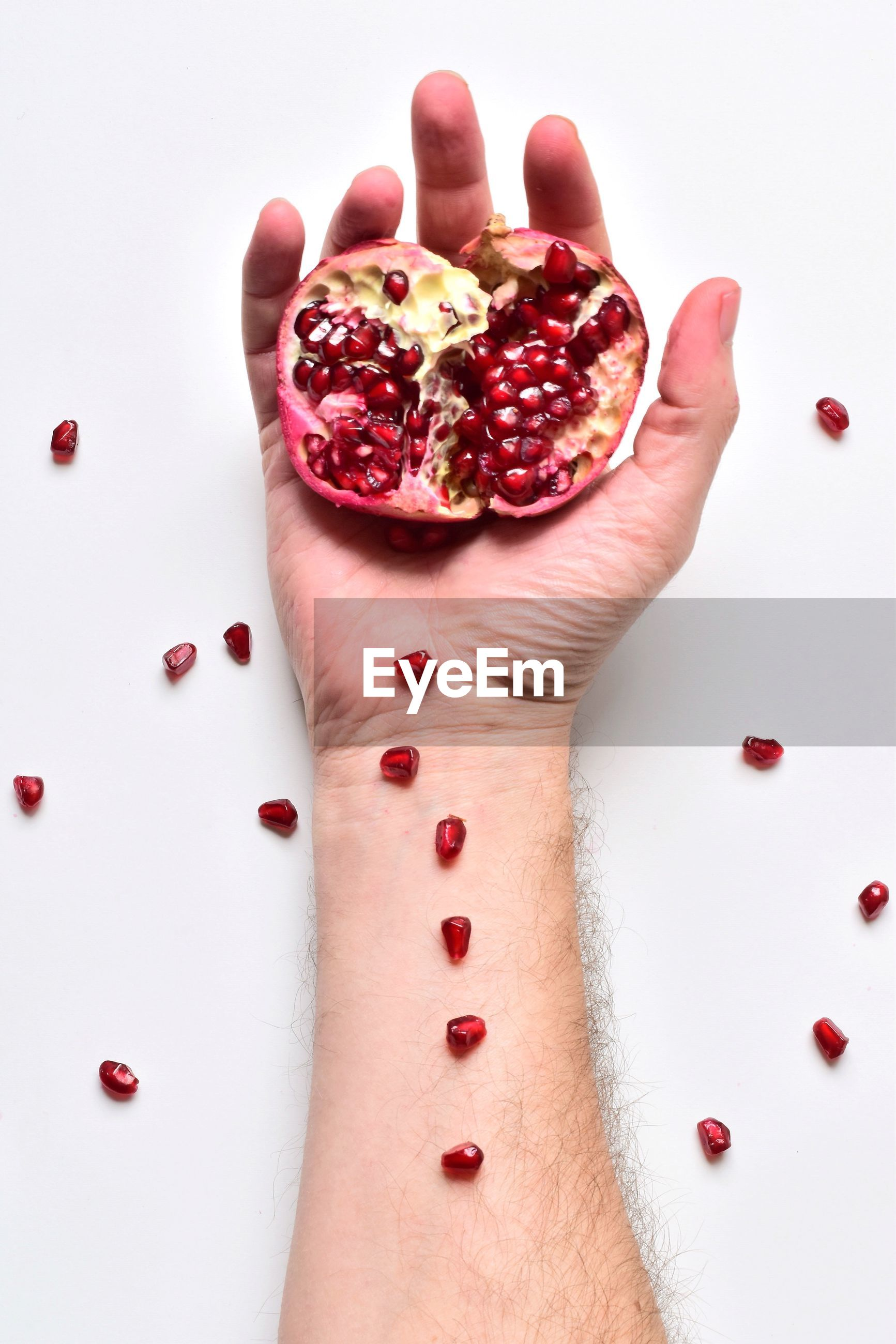 Cropped hand of man holding pomegranate over white background