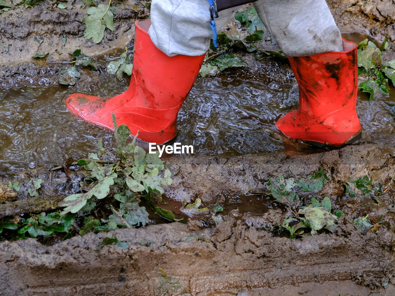 low section, one person, human leg, body part, shoe, human body part, real people, day, standing, lifestyles, nature, outdoors, unrecognizable person, plant, wet, land, red, boot, dirt, mud, dirty, messy, human foot, human limb
