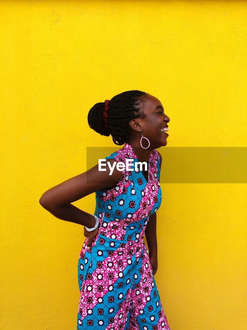 standing, wall - building feature, one person, three quarter length, yellow, real people, childhood, lifestyles, smiling, indoors, women, child, looking, looking away, happiness, fashion, yellow background