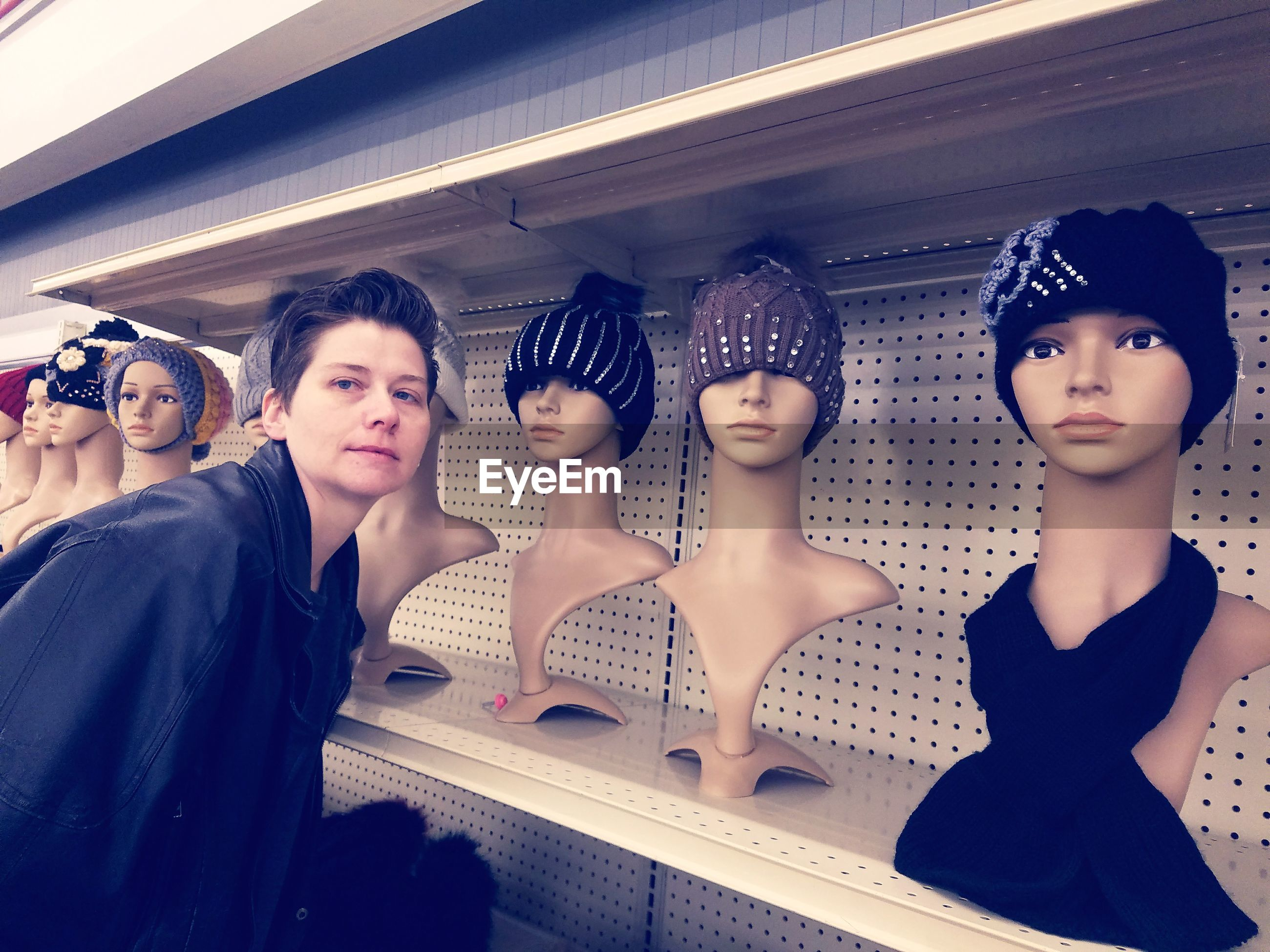 Portrait of woman by mannequins on shelf at store