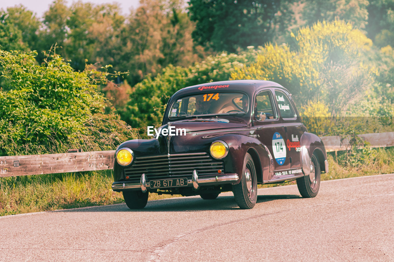 transportation, mode of transportation, land vehicle, day, land, plant, motor vehicle, tree, nature, car, road, retro styled, field, stationary, no people, vintage car, sunlight, yellow, green color, outdoors