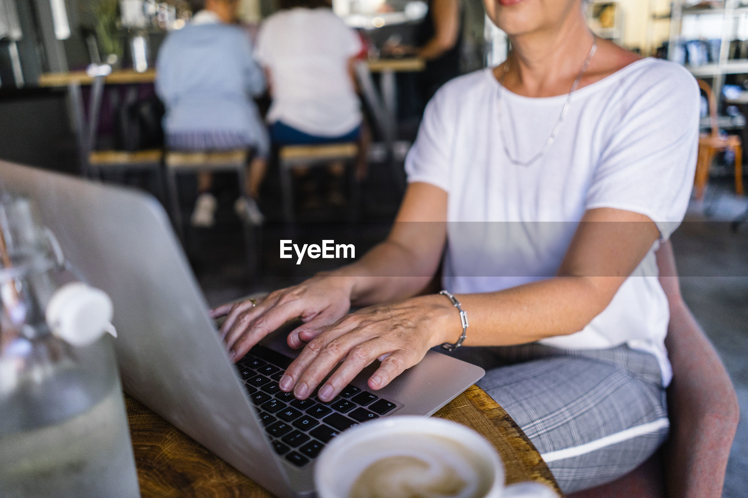 Midsection of woman using laptop on table in cafe