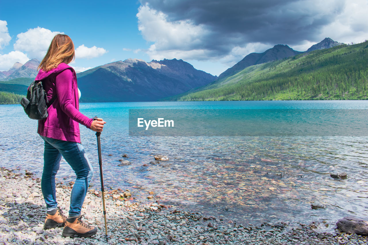 Rear view of woman standing on pebble stones by river against sky