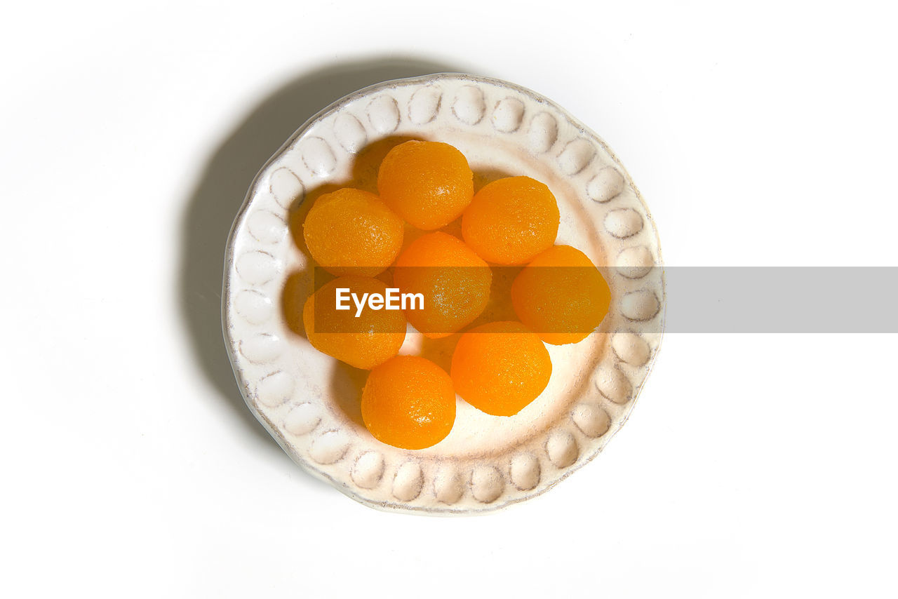 food, food and drink, freshness, studio shot, healthy eating, still life, white background, indoors, sweet food, directly above, wellbeing, no people, orange color, temptation, indulgence, sweet, fruit, close-up, high angle view, ready-to-eat, orange, egg yolk