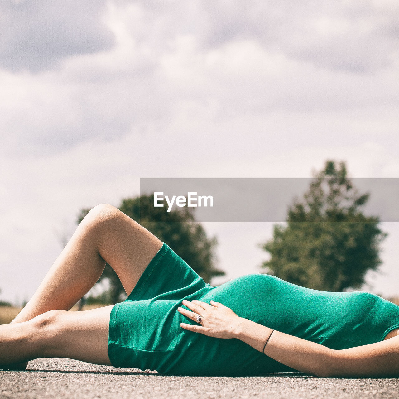 Mid section of a pregnant woman lying on ground