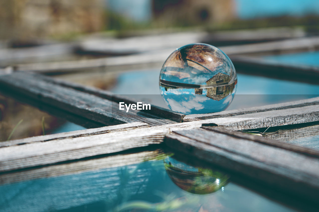 Close-Up Of Crystal Ball On Wooden Frame