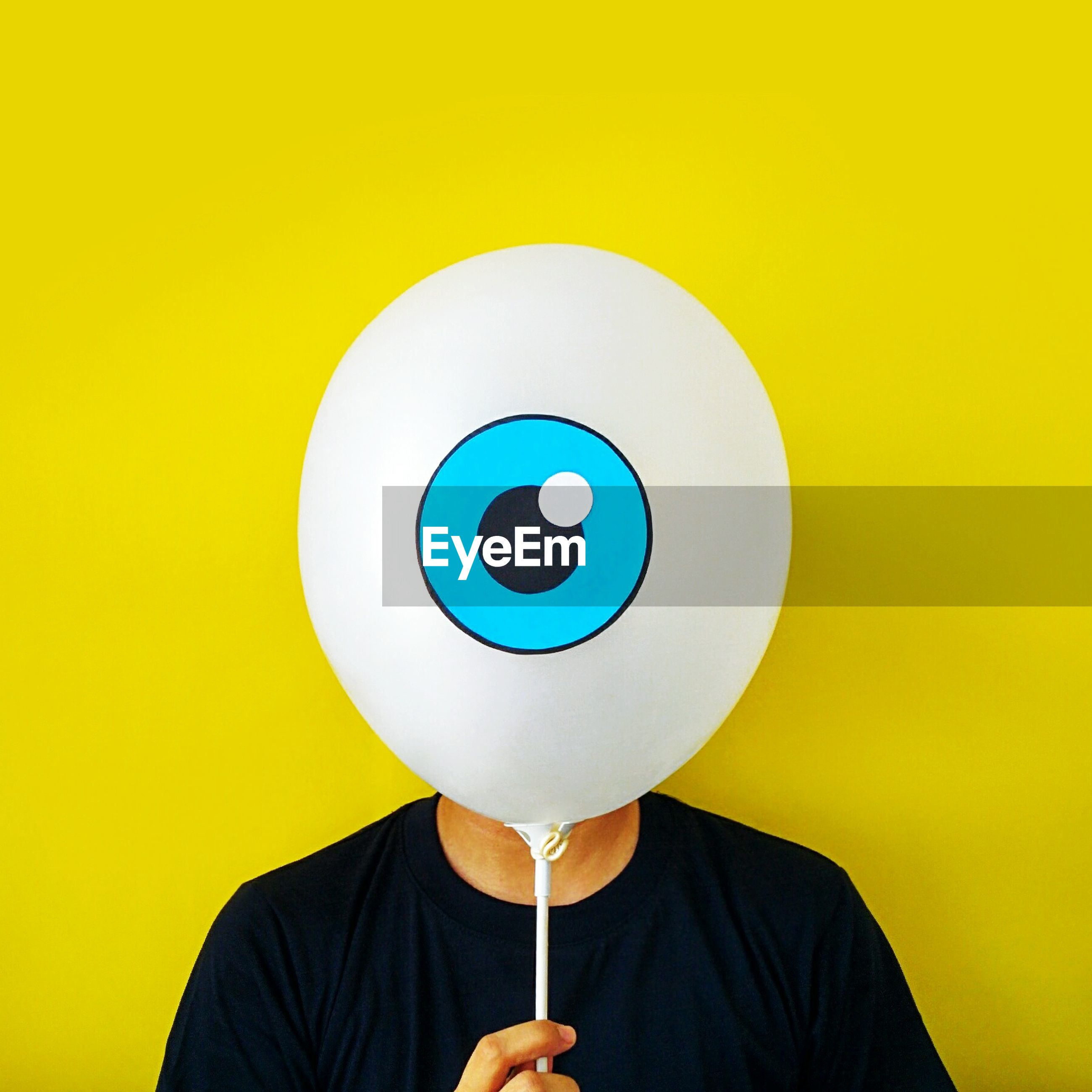 Man hiding face behind balloon against yellow background