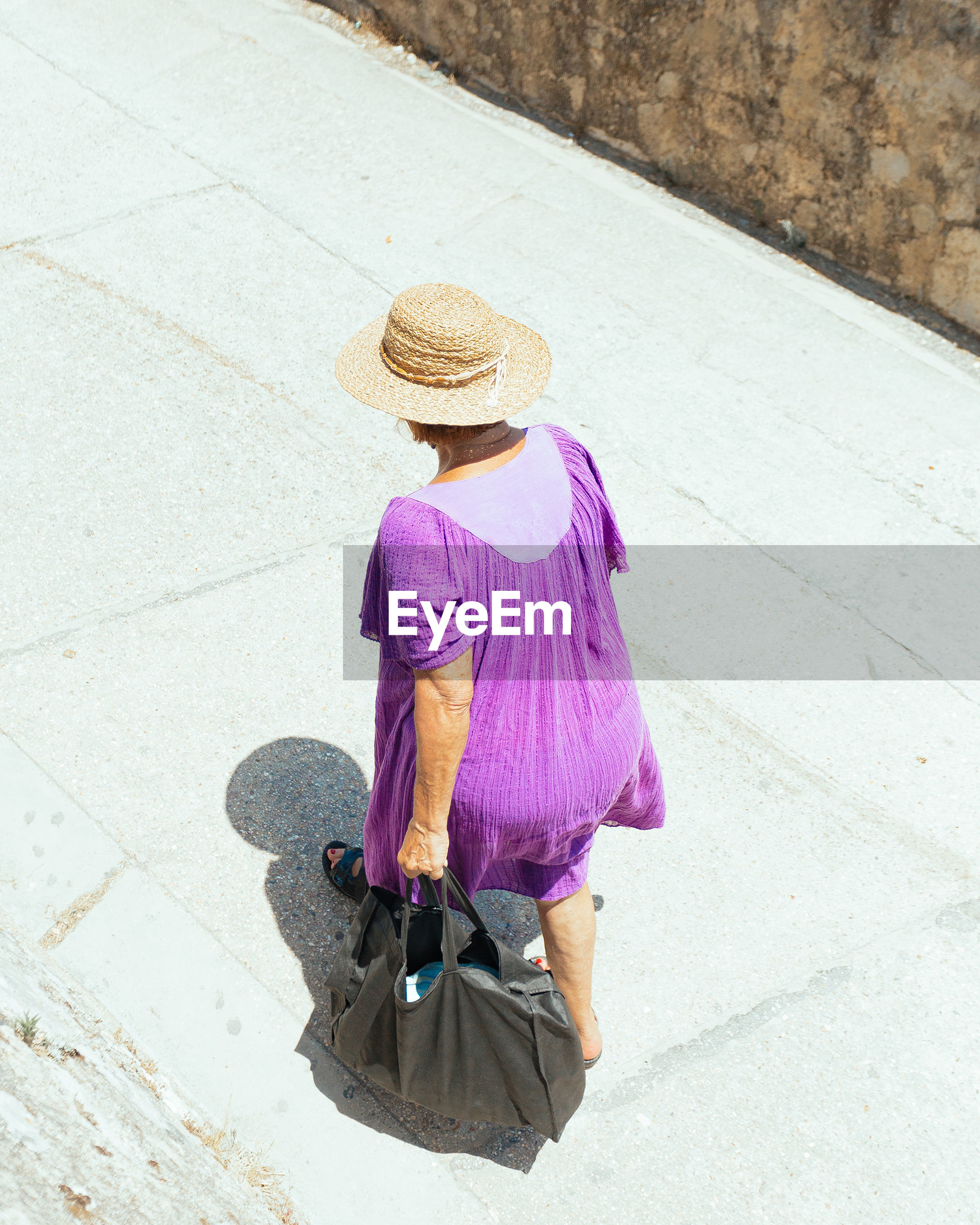 one person, hat, real people, women, rear view, casual clothing, clothing, walking, lifestyles, leisure activity, full length, day, high angle view, adult, bag, sun hat, purple, outdoors, pink color