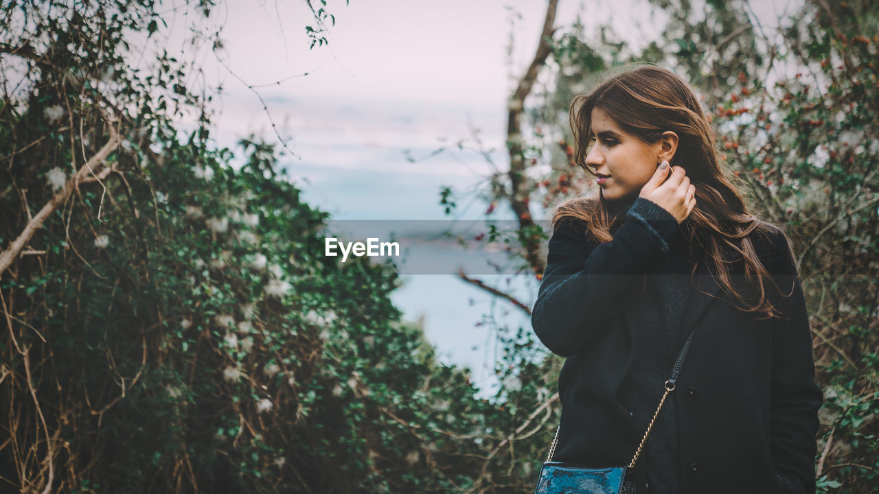Young Woman Looking Away While Standing Against Plants