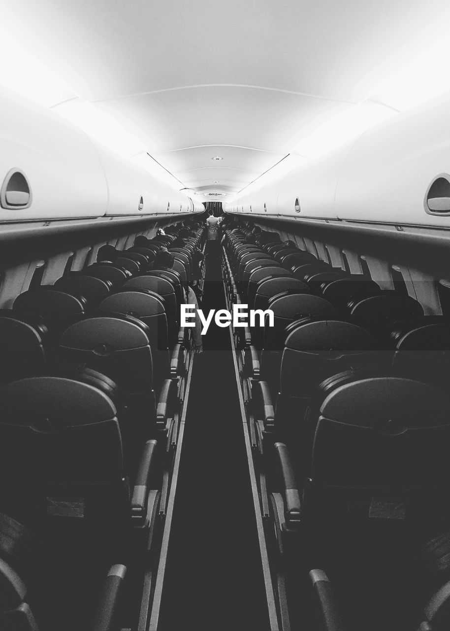 transportation, mode of transportation, vehicle interior, in a row, airplane, seat, air vehicle, travel, illuminated, public transportation, vehicle seat, lighting equipment, journey, empty, indoors, no people, absence, direction, diminishing perspective, rail transportation, light, aisle, ceiling