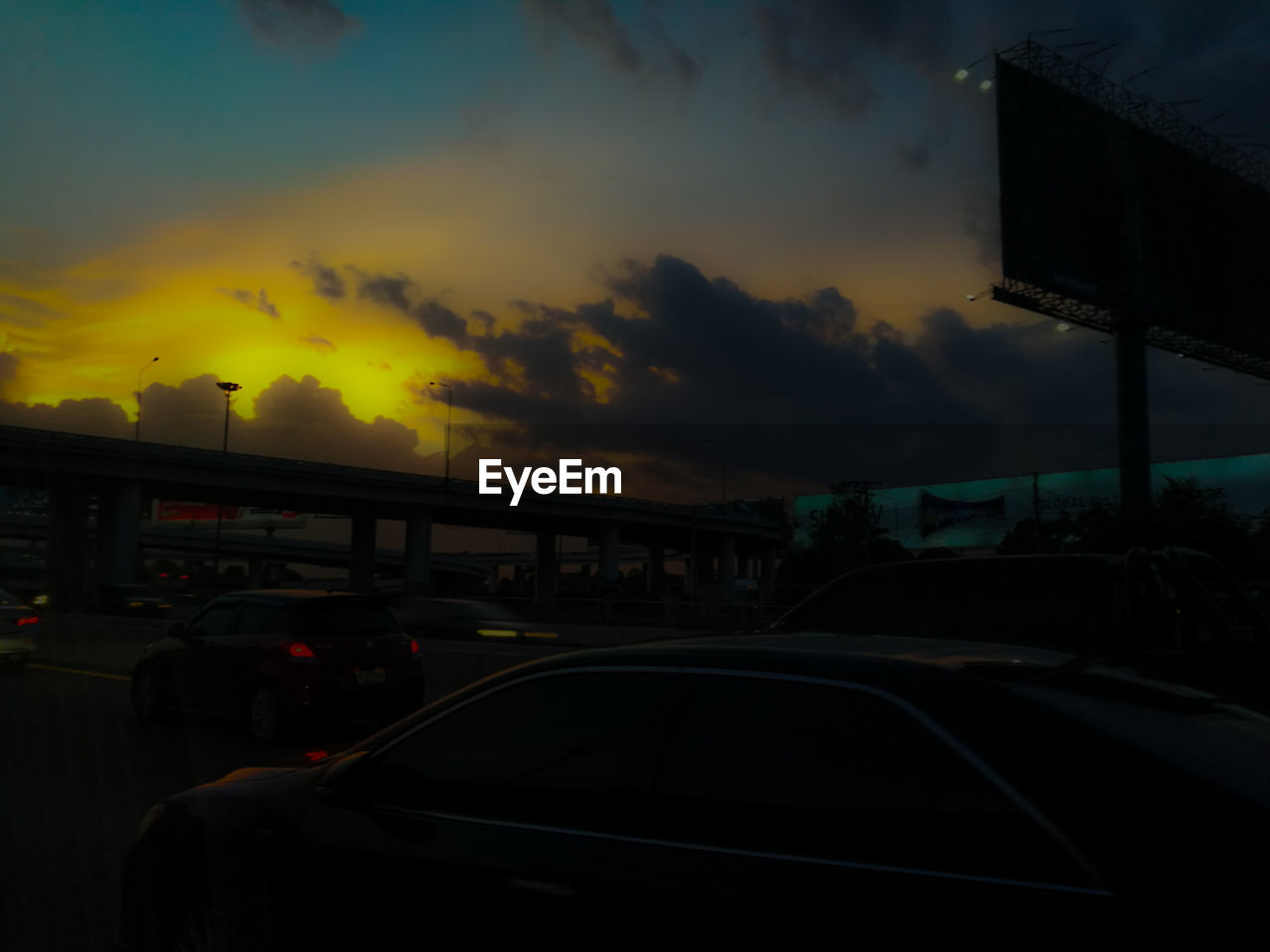 car, transportation, sunset, land vehicle, mode of transport, sky, cloud - sky, windshield, car interior, silhouette, outdoors, architecture, illuminated, city, nature, no people, day