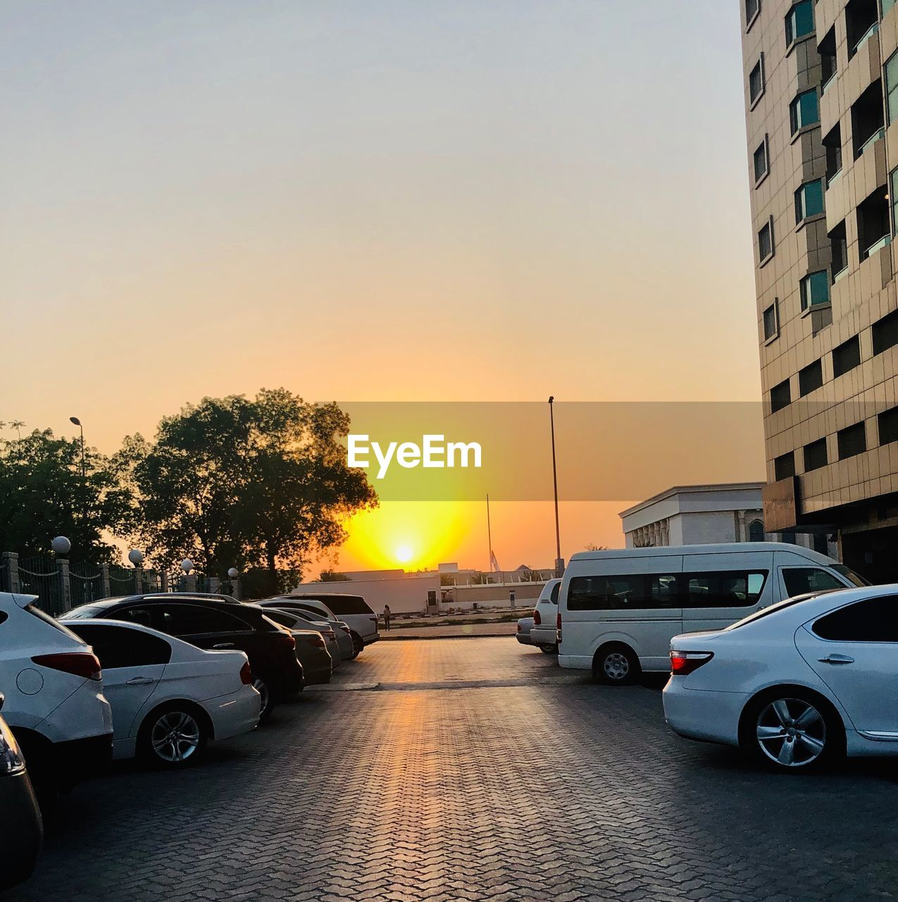 motor vehicle, car, mode of transportation, transportation, sunset, land vehicle, sky, city, architecture, road, nature, sun, building exterior, street, built structure, no people, orange color, tree, sunlight, clear sky, outdoors