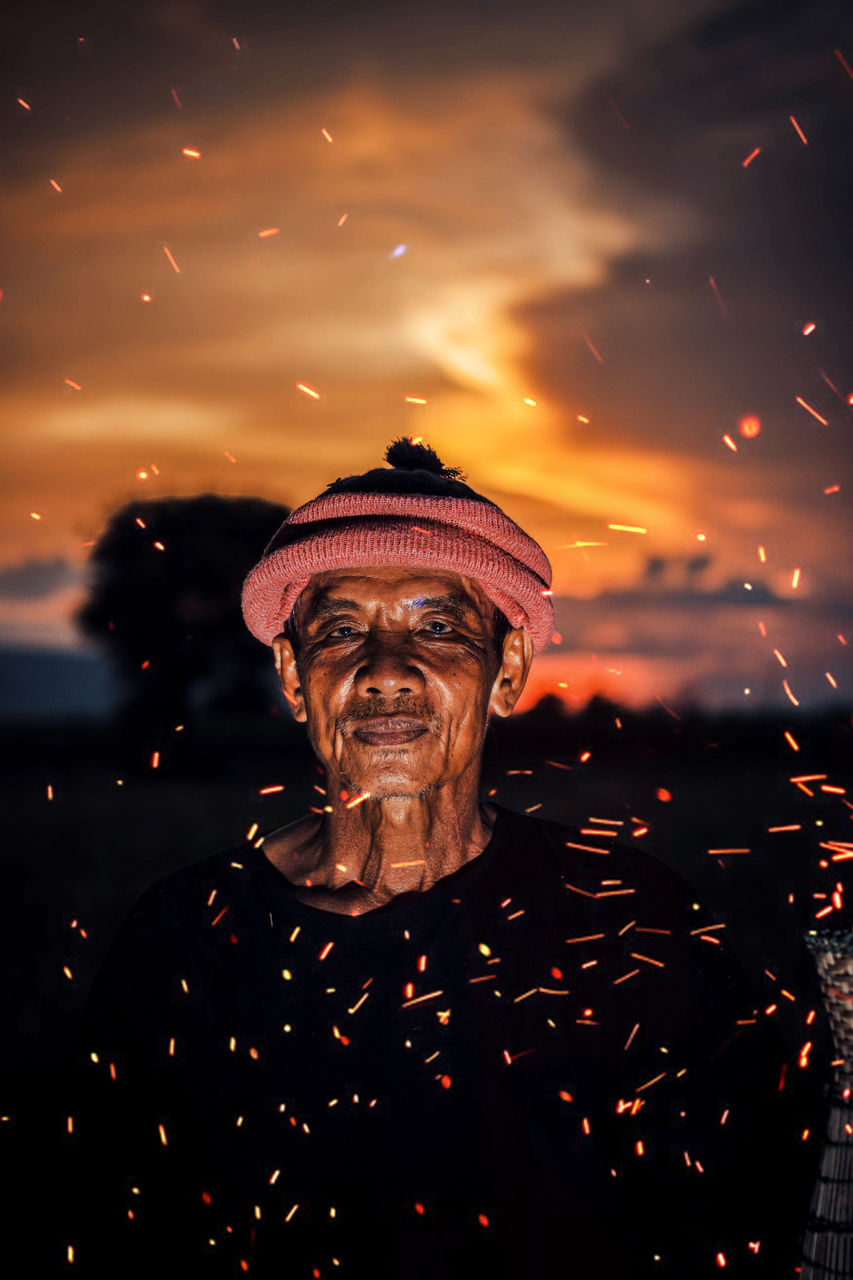 Portrait Of Smiling Senior Man In Fire Particles During Sunset