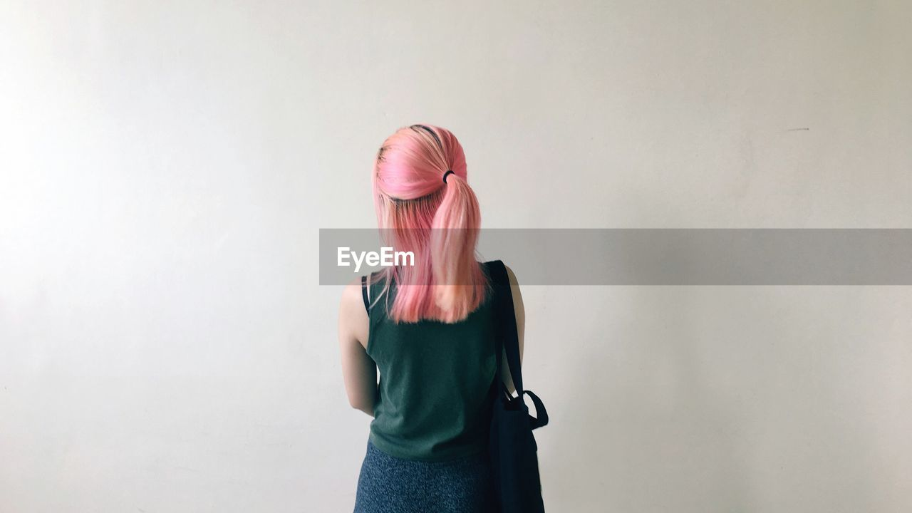 Rear View Of Woman With Dyed Hair Standing Against Wall