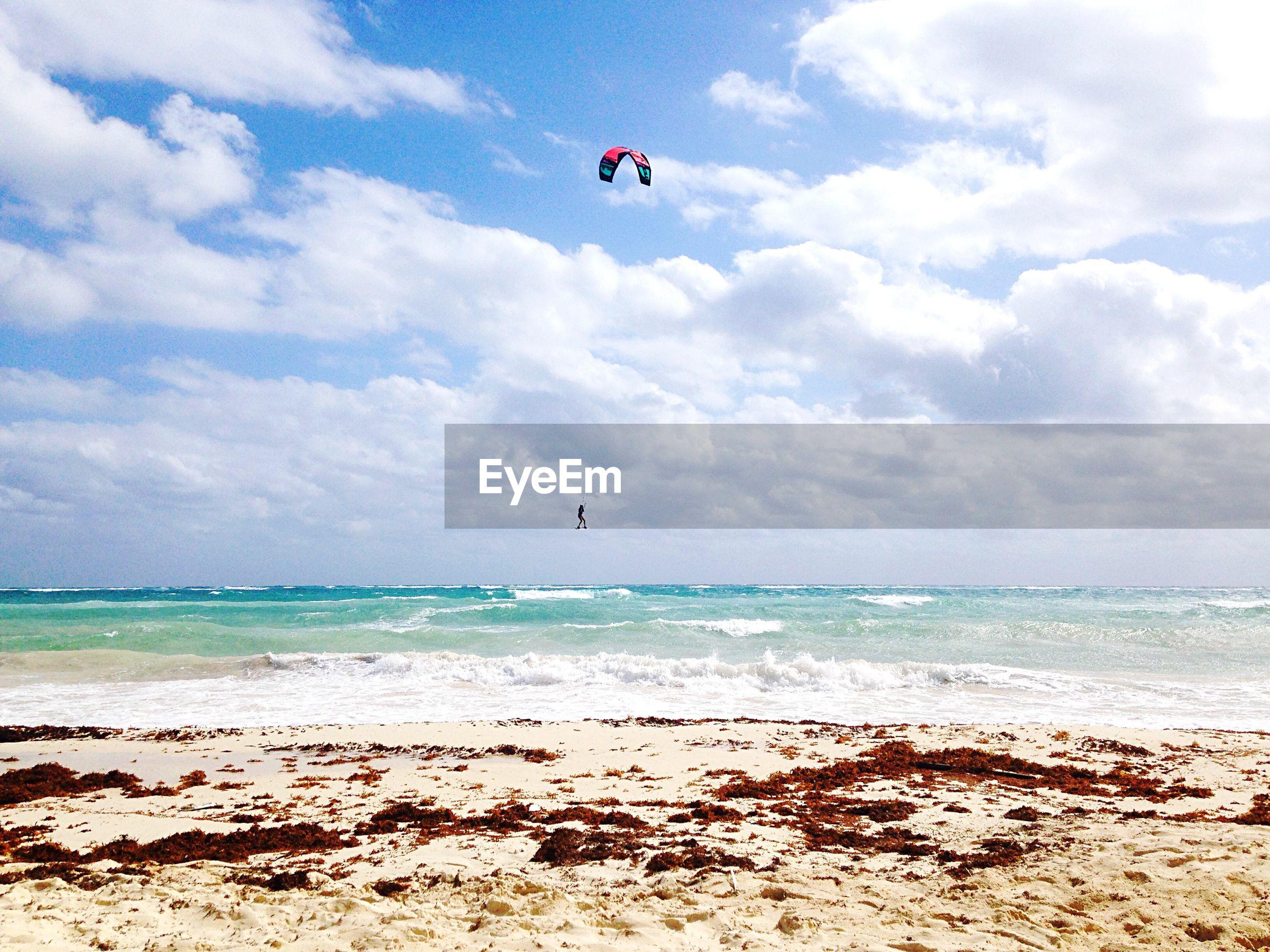 Person paragliding over beach