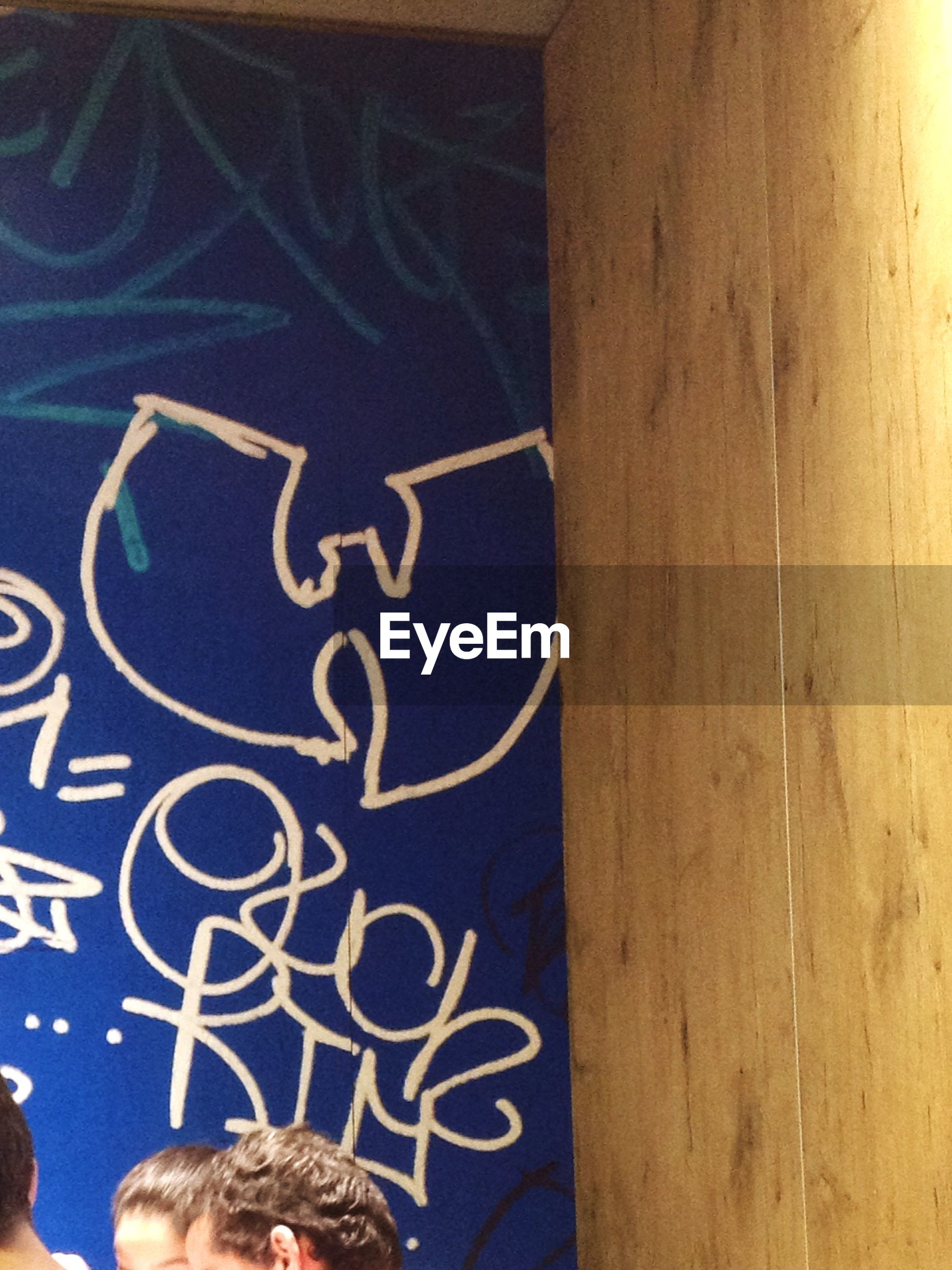 text, communication, western script, art, creativity, art and craft, human representation, capital letter, indoors, non-western script, close-up, graffiti, lifestyles, leisure activity, sign, wall - building feature, men