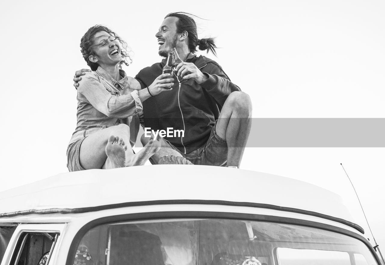 Couple toasting drink bottles on van against sky