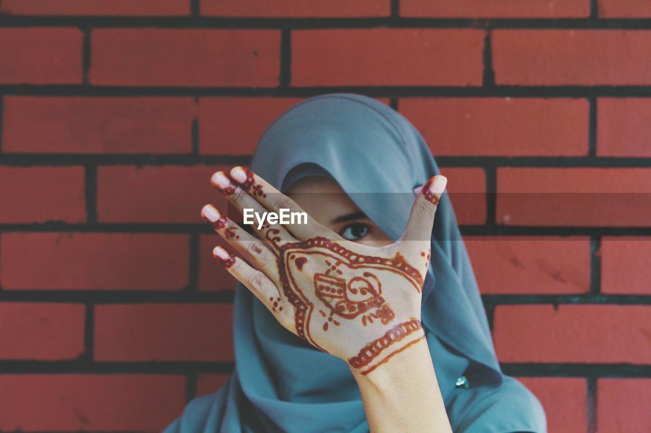 Portrait Of Young Woman With Henna Tattoo Hiding Face Against Wall