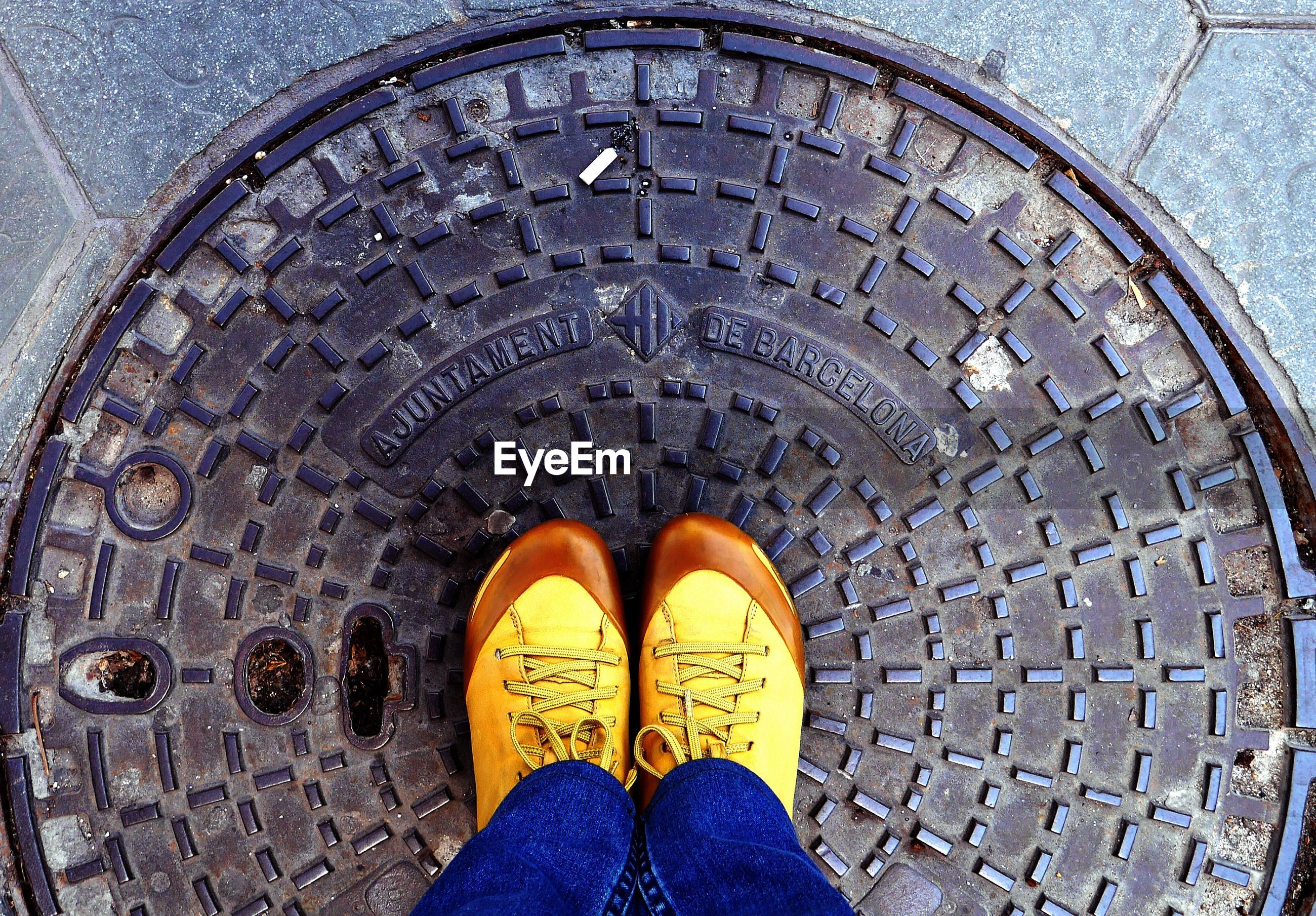 Low section view of man standing on manhole
