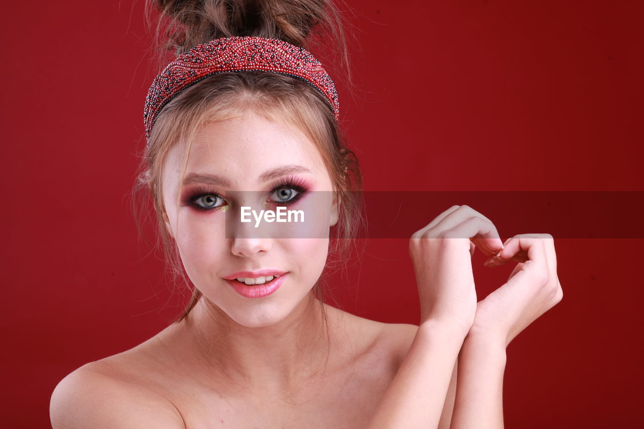 Portrait Of Beautiful Girl Making Heart Shape Against Red Background