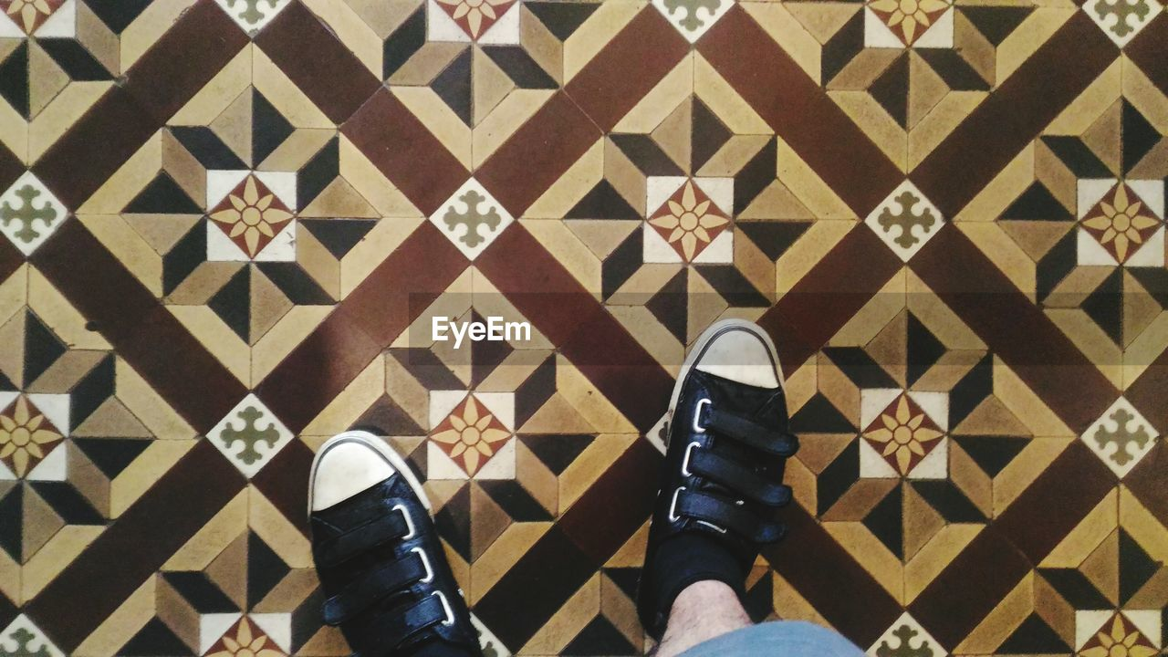shoe, low section, human leg, real people, personal perspective, standing, one person, human body part, human foot, high angle view, indoors, lifestyles, pair, pattern, men, canvas shoe, day, close-up, one man only, people