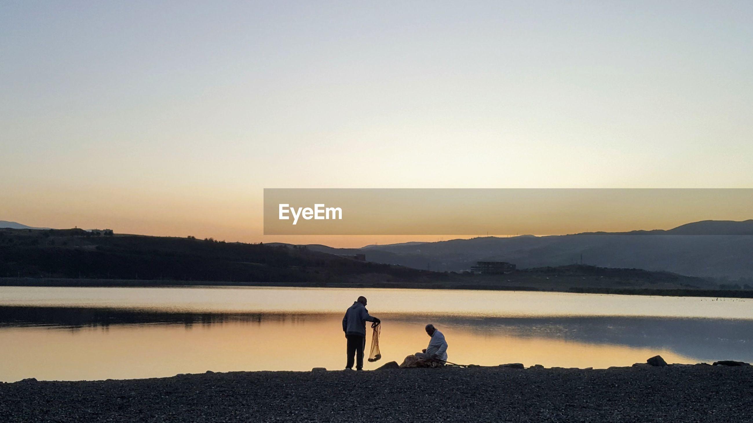 Men fishing in lake against sky during sunset