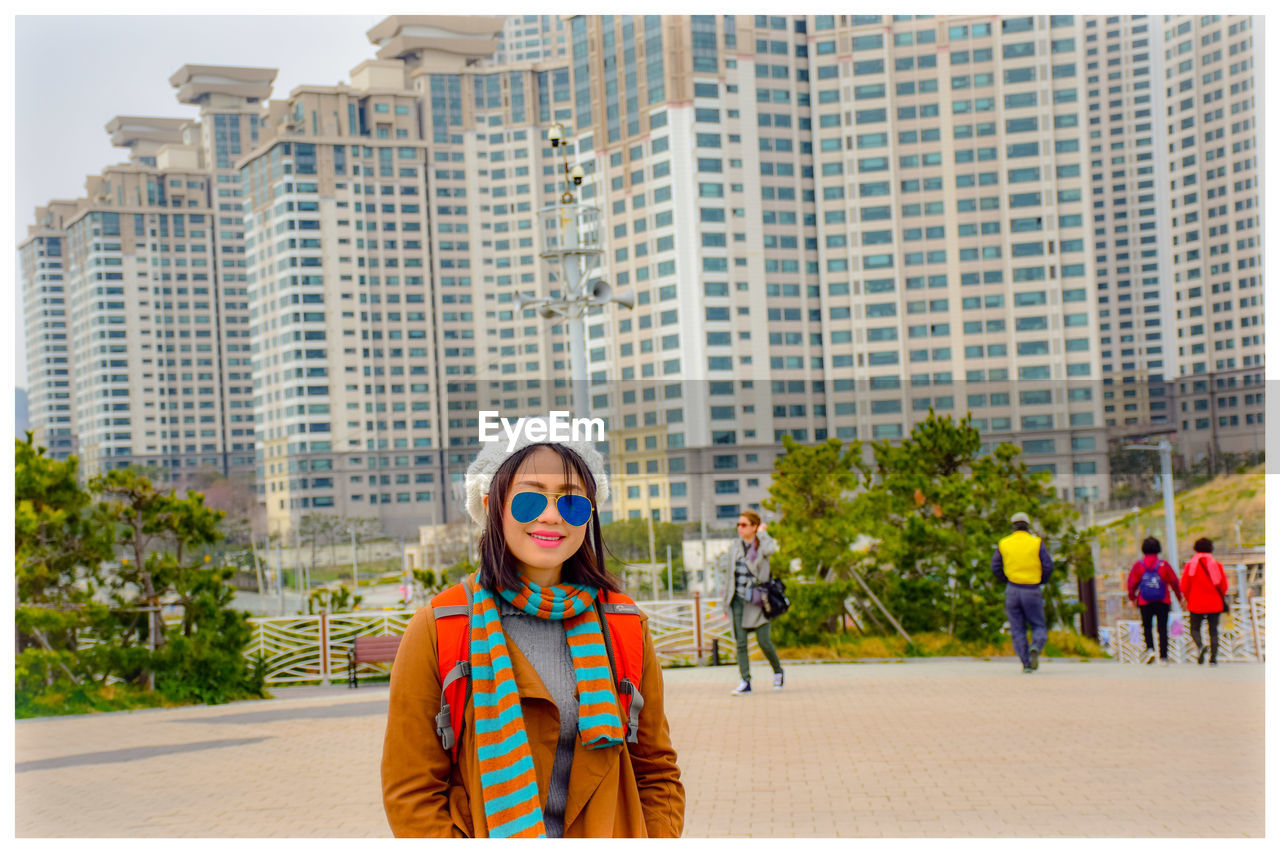 city, architecture, fashion, young adult, women, building exterior, portrait, standing, one person, front view, clothing, adult, young women, looking at camera, street, smiling, day, sunglasses, built structure, outdoors