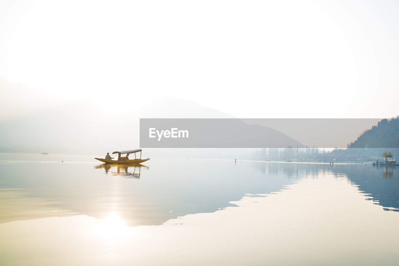 water, sky, scenics - nature, beauty in nature, tranquility, reflection, tranquil scene, lake, waterfront, mountain, nature, copy space, non-urban scene, nautical vessel, idyllic, fog, transportation, day, no people, outdoors