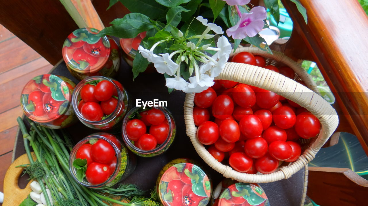 Close-Up Of Tomatoes In Glass Jars And Basket On Table