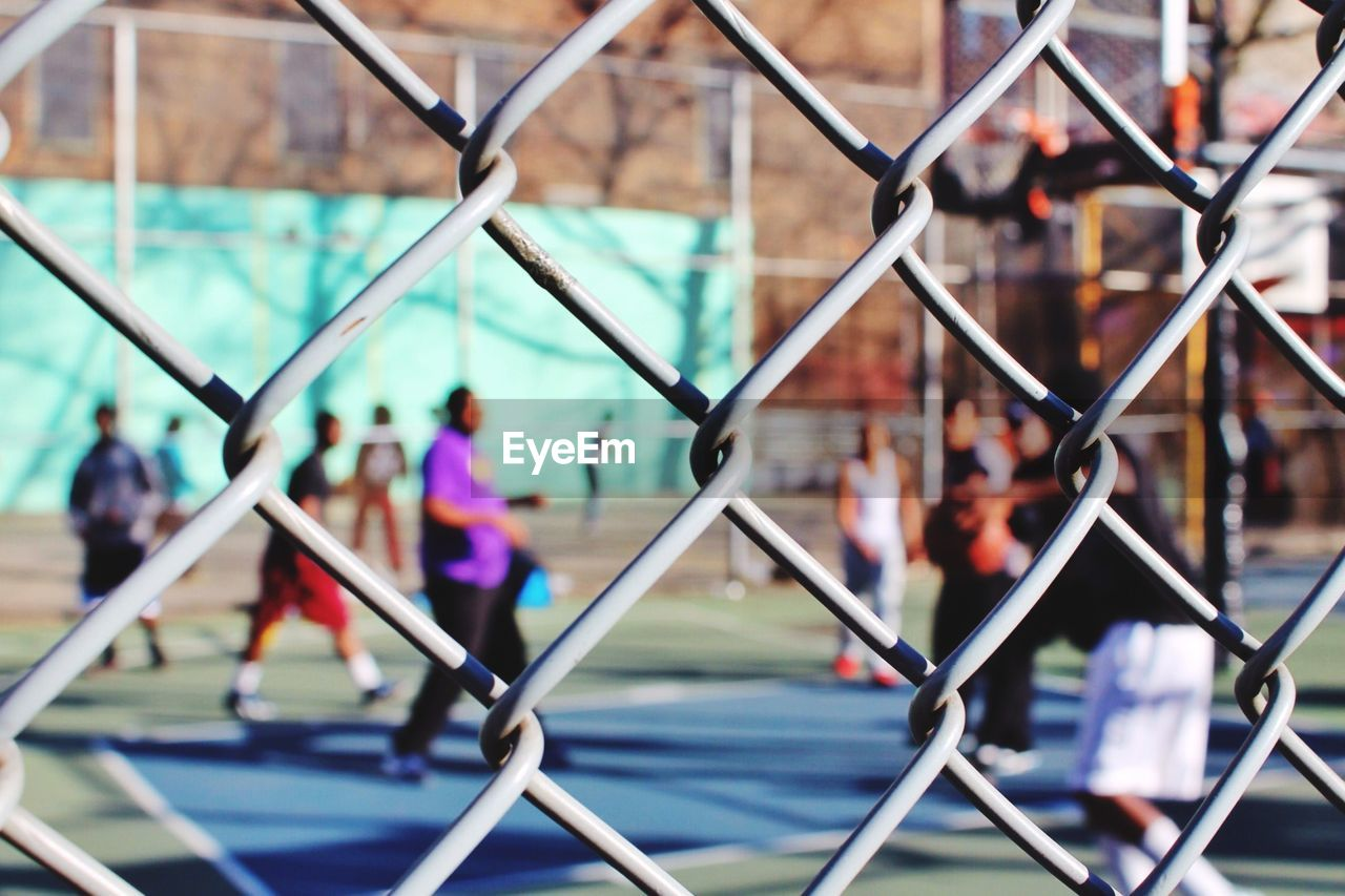 chainlink fence, focus on foreground, safety, metal, protection, togetherness, day, real people, outdoors, large group of people, lifestyles, close-up, group of people, friendship, city, architecture, sky, people