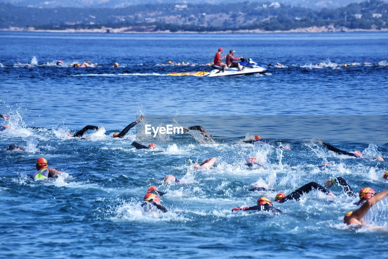water, group of people, sport, large group of people, crowd, sports race, nautical vessel, sea, competition, competitive sport, day, real people, nature, men, transportation, motion, aquatic sport, athlete, outdoors, effort, inflatable