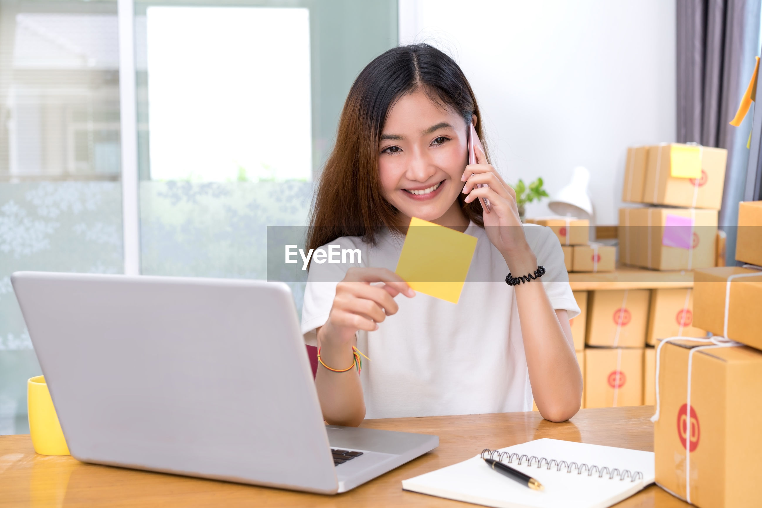 Smiling young woman holding adhesive note while talking on phone at office