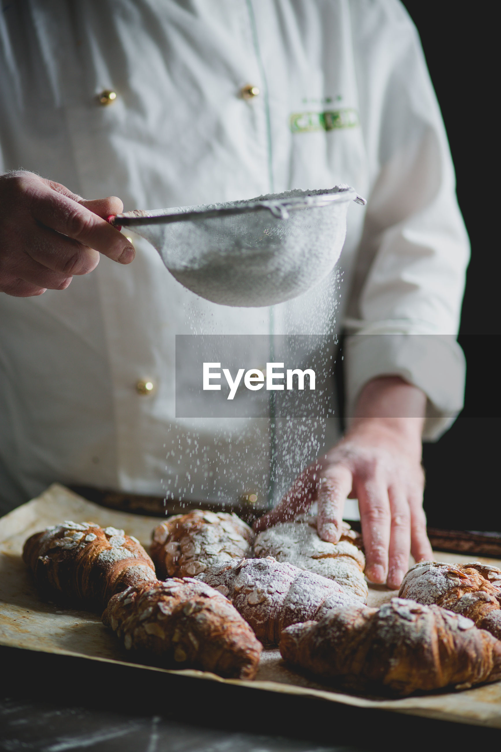 Midsection of chef sprinkling powdered sugar on croissants in bakery