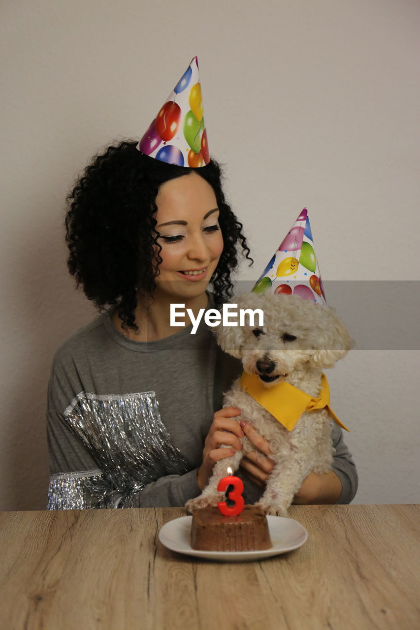 Smiling young woman celebrating birthday of dog