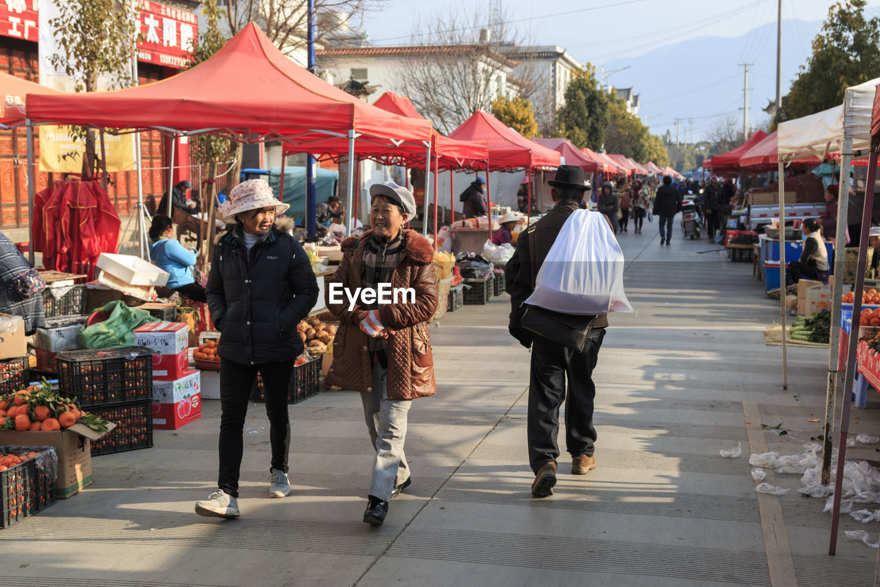 group of people, city, market, retail, real people, market stall, walking, women, adult, men, street, business, lifestyles, shopping, day, people, architecture, small business, full length, city life, outdoors, street market, consumerism, retail display
