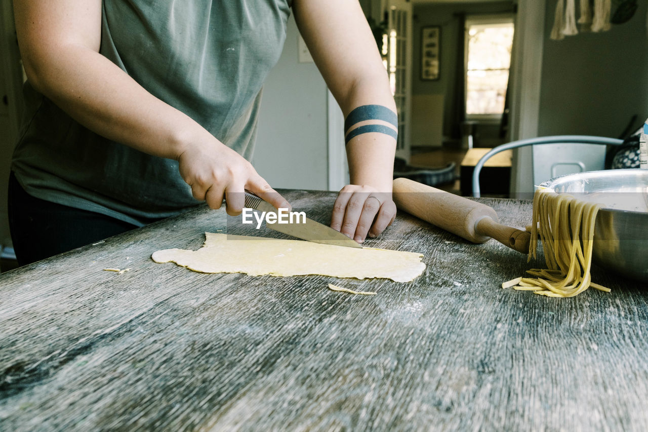 MIDSECTION OF PERSON PREPARING FOOD ON TABLE AT KITCHEN