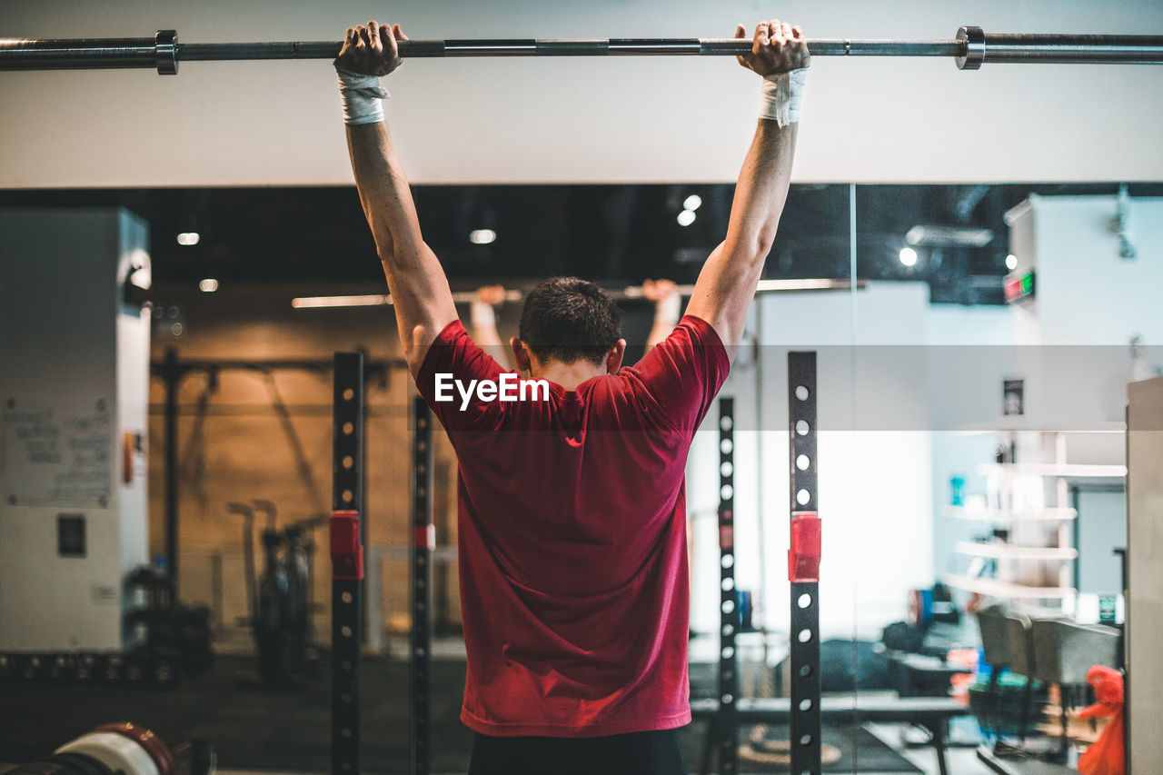 gym, determination, sport, lifestyles, strength, sports training, one person, muscular build, exercising, arms raised, weight, indoors, weight training, human arm, real people, vitality, healthy lifestyle, rear view, adult, leisure activity, effort, self improvement, human limb, cross training