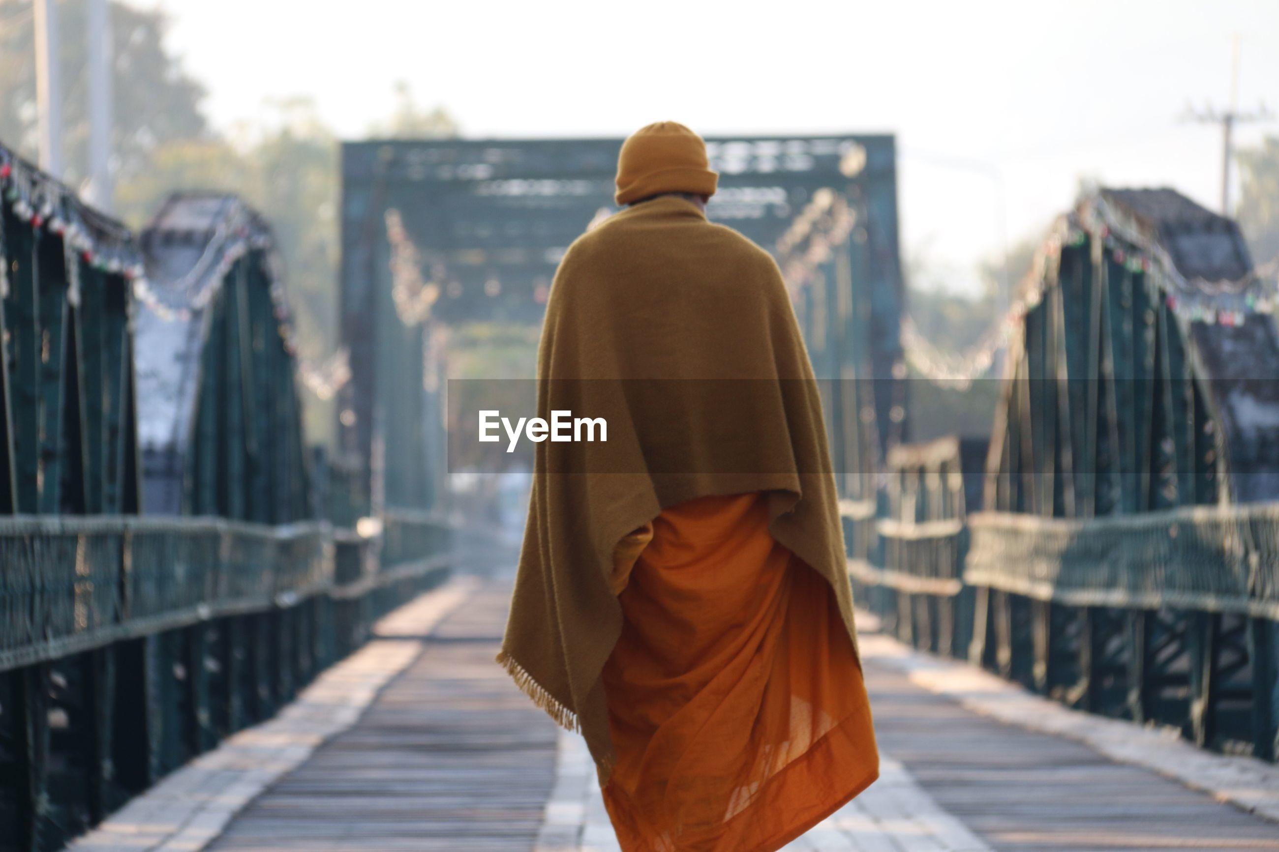 Rear view of monk walking on footbridge